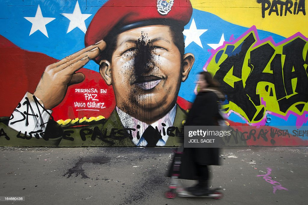 A woman walks past a graffiti representing Venezuela's late president Hugo Chavez on March 26, 2013 in Paris. AFP PHOTO/ JOEL SAGET