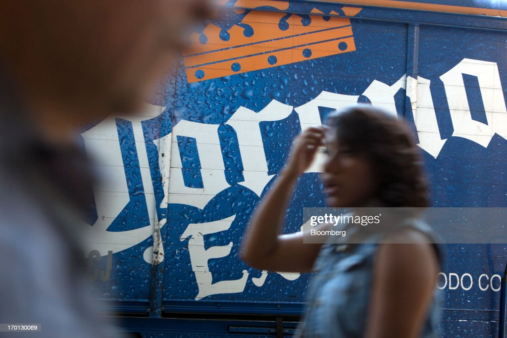 A woman walks past a Grupo Modelo SAB delivery truck with then logo for their Corona beer in Mexico City, Mexico, on Thursday, June 6, 2013. Heineken NV and Grupo Modelo SAB, the dominant brewers in Mexico with brands such as Dos Equis and Corona, are nearing the end of an almost three-year-old government antitrust probe. Photographer: Susana Gonzalez/Bloomberg via Getty Images