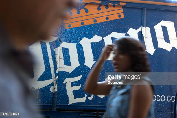 A woman walks past a Grupo Modelo SAB delivery truck with then logo for their Corona beer in Mexico City Mexico on Thursday June 6 2013 Heineken NV...