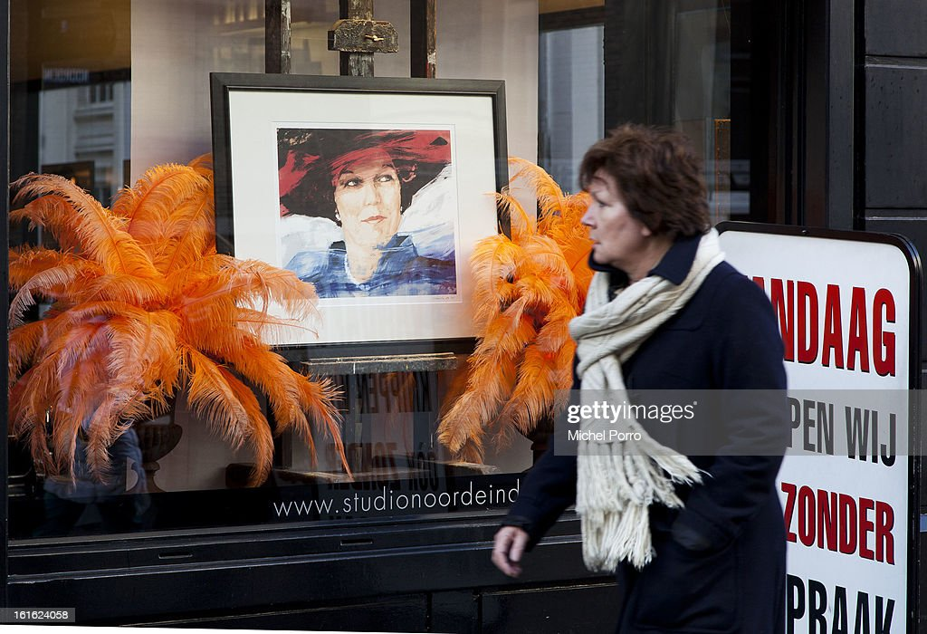 A woman walks past a hair salon near the Noordeinde Palace displaying a portrait of Queen Beatrix as the nation looks forward to the upcoming coronation of King Willem Alexander on February 13, 2013 in The Hague, Netherlands. The coronation Of Prince Willem Alexander will happen on April 30
