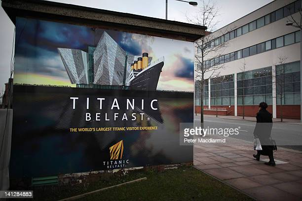A woman walks past a hoarding advertising the Titanic Belfast attraction in The Titanic Quarter on March 13 2012 in Belfast Northern Ireland...