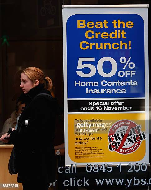 A woman walks past a home insurance sign which refers to the current financial crisis on October 8 2008 in Glasgow Scotland The UK government has...