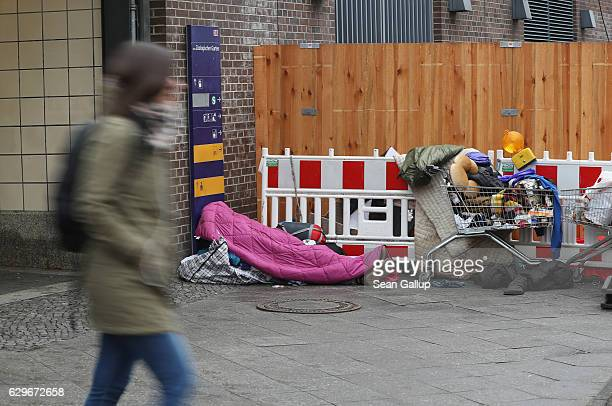 A woman walks past a homeless person covered by a sleeping bag on December 14 2016 in Berlin Germany An estimated 3000 to 6000 homeless people live...