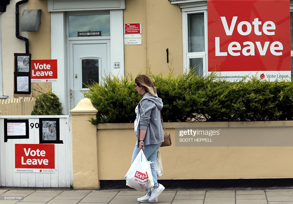 A woman walks past a house where 'Vote Leave' boards are displayed in Redcar, north east England on June 27, 2016 Britain's historic decision to leave the 28-nation bloc has sent shockwaves through the political and economic fabric of the nation. It has also fuelled fears of a break-up of the United Kingdom with Scotland eyeing a new independence poll, and created turmoil in the opposition Labour party where leader Jeremy Corbyn is battling an all-out revolt. / AFP / Scott Heppell