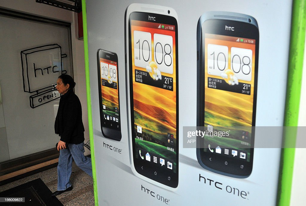 A woman walks past a HTC store in the Younghe district of New Taipei City on November 11, 2012. Taiwan's leading smartphone maker HTC said it has reached a global settlement with technology giant Apple, bringing an end to all outstanding litigation between the two companies. AFP PHOTO / Mandy CHENG