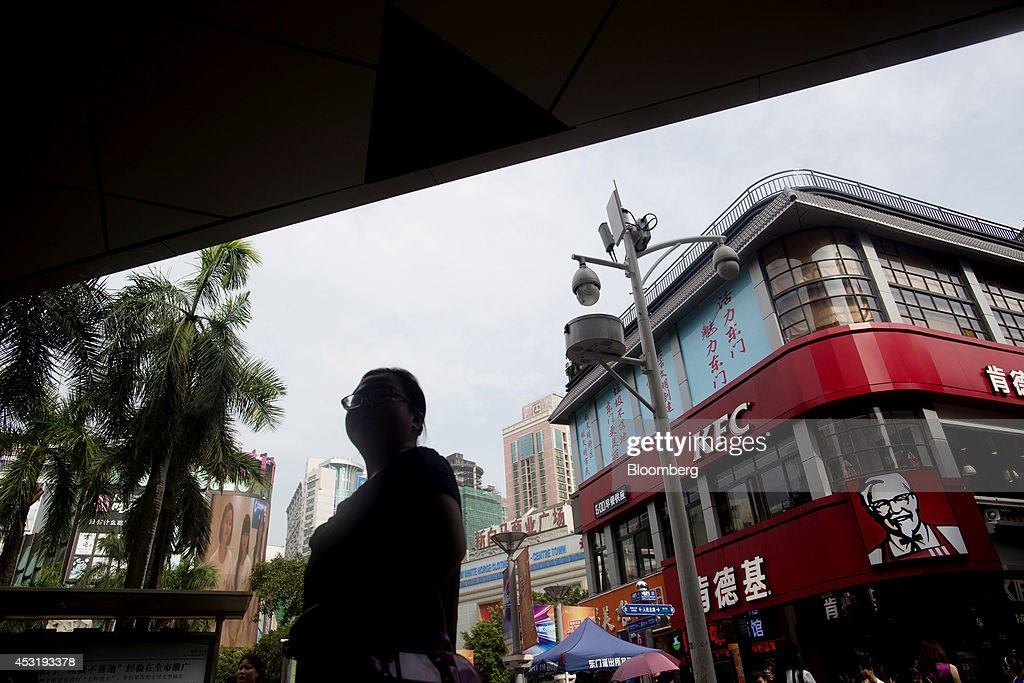 A woman walks past a KFC restaurant, operated by Yum! Brands Inc., in the pedestrianized Dongmen area of Shenzhen, China, on Monday, Aug. 4, 2014. Yum, owner of KFC and Pizza Hut, said its China team is trying to regain customers after a supply chain scare has recently hurt results. Photographer: Brent Lewin/Bloomberg via Getty Images