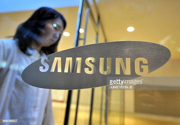 A woman walks past a logo of Samsung Electronics at its showroom in Seoul on January 7 2010 South Korea's Samsung Electronics said it expects to post...
