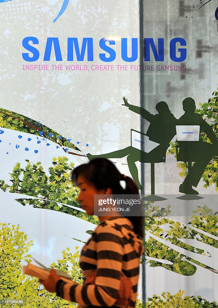 A woman walks past a logo of Samsung Electronics at their headquarters in Seoul on November 6, 2013. Samsung Electronics promised better shareholder returns, dismissed fears over smartphone market saturation and signalled a more aggressive acquisitions policy Wednesday at a rare analysts' briefing to boost its flagging stock price. AFP PHOTO / JUNG YEON-JE