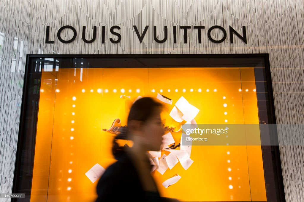A woman walks past a Louis Vuitton store, operated by LVMH Moet Hennessy Louis Vuitton SA, at the Siam Paragon shopping mall in Bangkok, Thailand, on Tuesday, Feb. 5, 2013. Thai inflation may average 2.8 percent this year, the Bank of Thailand said. Photographer: Brent Lewin/Bloomberg via Getty Images