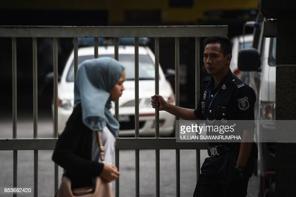 A woman walks past a Malaysian policeman holding the gate to the forensics wing of the Hospital Kuala Lumpur where the body of Kim JongNam is being...