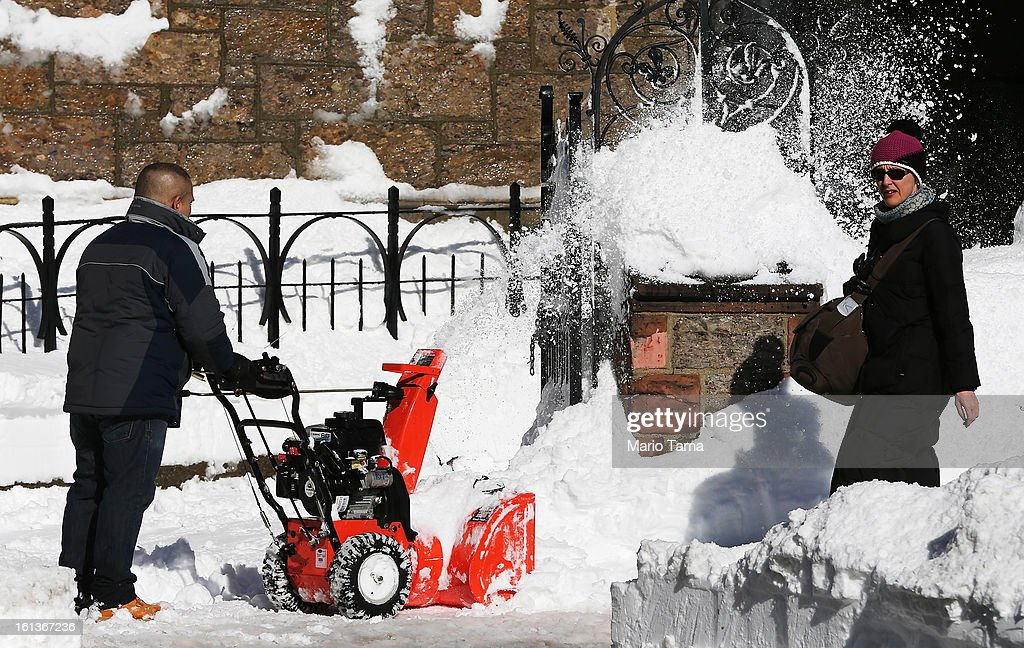 A woman walks past a man clearing snow from a sidewalk in the Back Bay neighborhood following a powerful blizzard on February 10, 2013 in Boston, Massachusetts. The storm dumped more than two feet of snow in parts of New England and more than 200,000 Massachusetts customers remain without power.