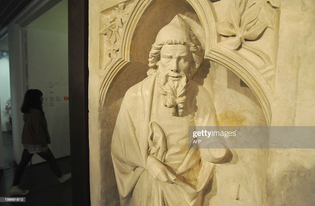 A woman walks past a marble named 'Relief of Saint Joachim', from Retrofacade Reims Cathedral in France during a press conference in Taipei on November 19, 2012. The Metropolitan Museum of Art selected the Taiwan Museum or Educational Institutions to gift the art collection of 100 medieval plaster statues. AFP PHOTO / Mandy CHENG