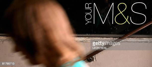 A woman walks past a Marks and Spencer sign at Green Park tube station in central London on July 2 2008 British retailer Marks and Spencer shares...