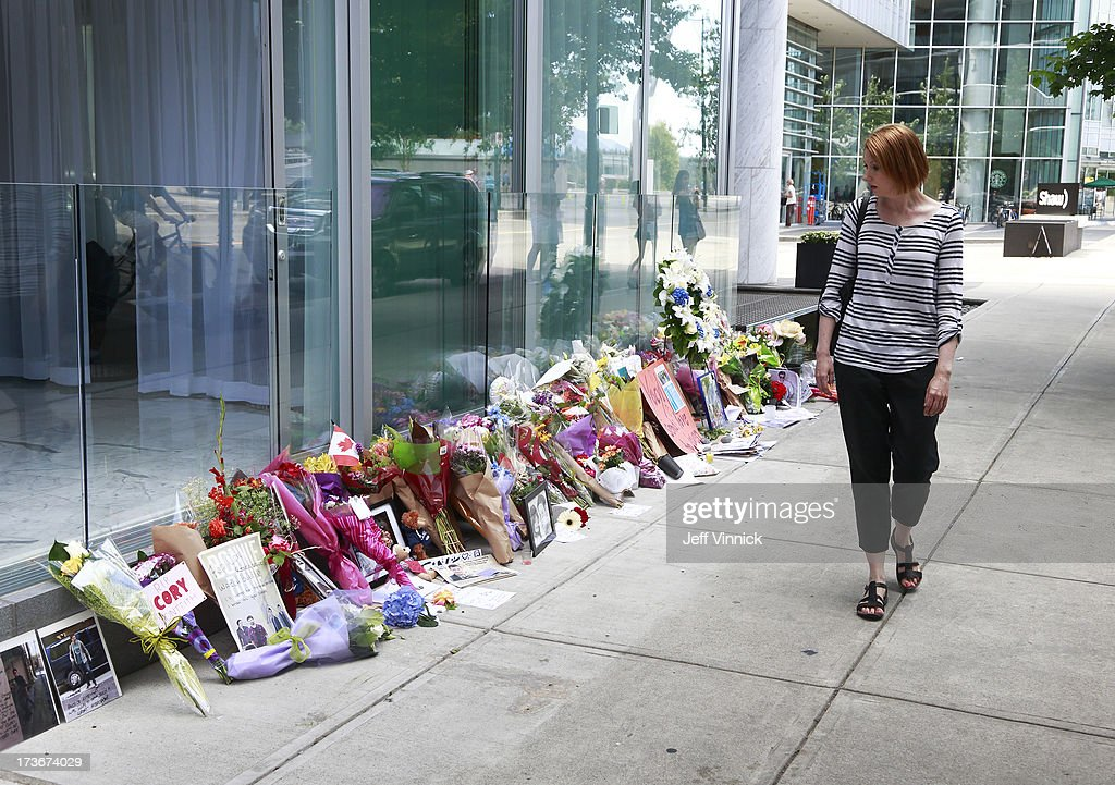 A woman walks past a memorial to deceased actor Cory Monteith outside the Fairmont Pacific Rim Hotel on July 16, 2013 in Vancouver, British Columbia, Canada. The B.C. Coroners Service released results of Monteith's autopsy today and found the 31-year-old's cause of death was a mixed drug toxicity involving heroin and alcohol.