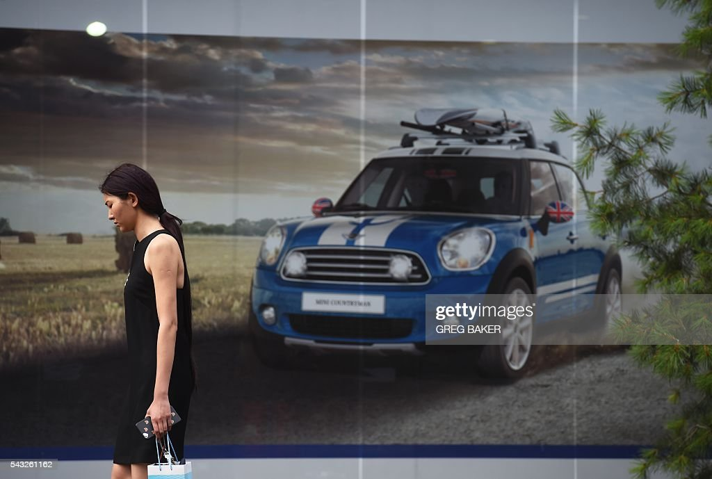 A woman walks past a Mini showroom in Beijing on June 27, 2016. Britain's vote to leave the European Union has added new uncertainties to the world economy at a time when downward pressures on China's economy are mounting, Premier Li Keqiang said on June 27 at a World Economic Forum meeting in the Chinese city of Tianjin. / AFP / GREG