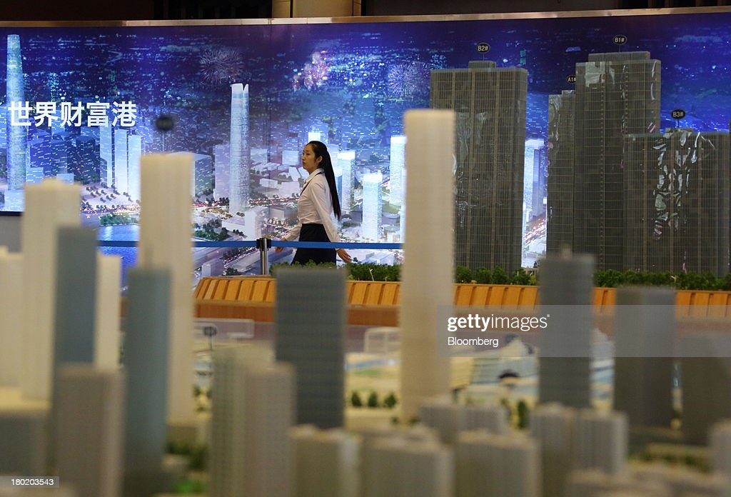 A woman walks past a model of the city of Dalian at the registration point for the World Economic Forum Annual Meeting of The New Champions 2013 in Dalian, China, on Tuesday, Sept. 10, 2013. The World Economic Forum Annual Meeting Of The New Champions 2013 will be held in Dalian from Sept. 11 to 13. Photographer: Tomohiro Ohsumi/Bloomberg via Getty Images