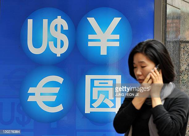 A woman walks past a money exchange sign in Seoul on October 14 2010 A senior Japanese finance ministry official has apologised for his minister's...