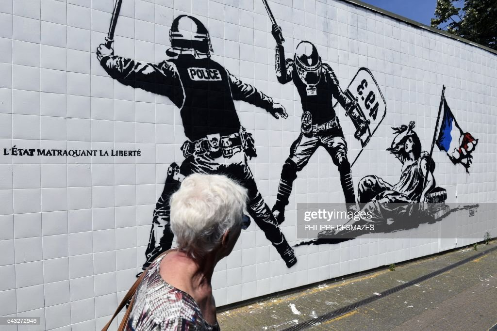 A woman walks past a mural by French artist Goin on June 27, 2016 in Grenoble, southeastern France. Mayor of Grenoble Eric Piolle (EELV) Monday invoked the freedom of expression after the controversy surrounding an urban art work deemed 'anti-police,' and created as part of a festival sponsored by the municipality. / AFP / PHILIPPE