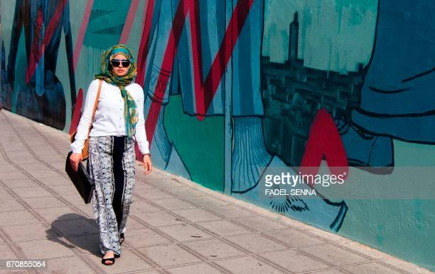 A woman walks past a mural during the 'Jidar' street art festival in the capital Rabat on April 20 2017 / AFP PHOTO / FADEL SENNA