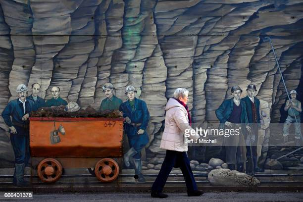 A woman walks past a mural of iron ore miners on February 14 2017 in AlgrangeFrance The people of the French Rust Belt are expected to play a key...