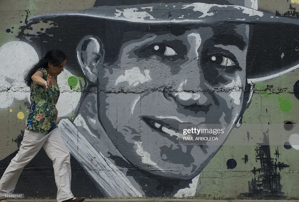 A woman walks past a mural of legendary tango singer Carlos Gardel during a ceremony commemorating the 78th anniversary of his death, in Medellin, Colombia on June 24, 2013. Gardel died 78 years ago in an airplane crash in the Olaya Herrera airport of Medellin. AFP PHOTO/ Raul ARBOLEDA