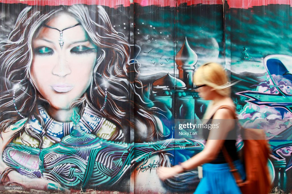 A woman walks past a mural on a shophouse along Haji Lane on April 1, 2013 in Singapore. A shophouse is a vernacular architectural building type that is commonly seen in areas such as urban Southeast Asia. Shophouses are mostly two or three stories high, with a shop on the ground floor for mercantile activity and a residence above the shop. This pre-industrial form of urban units, prevalent in 19th and early 20th century Southeast Asian towns, cities and commercial centres, literally housed everything from work to home. Today, these buildings are recognised for their significance not only as an architectural heritage but more importantly as a reflection of the island's societal history and development.