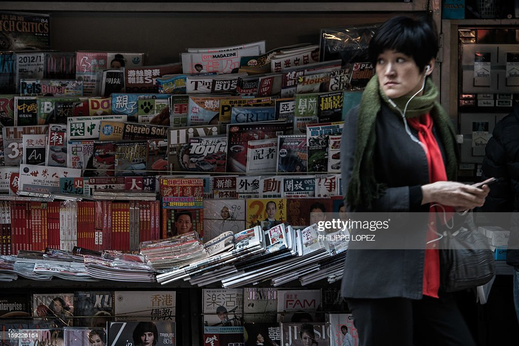 A woman walks past a news stand in a street in Hong Kong on January 10, 2013. Journalists in Hong Kong on January 10 slammed a government bid to restrict access to information about company directors, after a series of investigative reports into the hidden wealth of Chinese officials. AFP PHOTO / Philippe Lopez