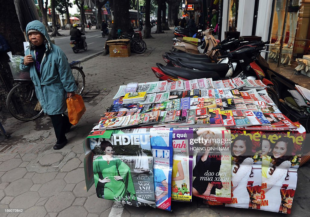 A woman walks past a newsstand in downtown Hanoi on January 11, 2013. At a recent national meeting on propaganda works, propaganda officials revealed they prepared hundreds of 'online writers' to deal with the current online anti-state propaganda led by dissident bloggers. Last month Prime Minister Nguyen Tan Dung ordered a new crackdown on online dissent. AFP PHOTO / HOANG DINH Nam
