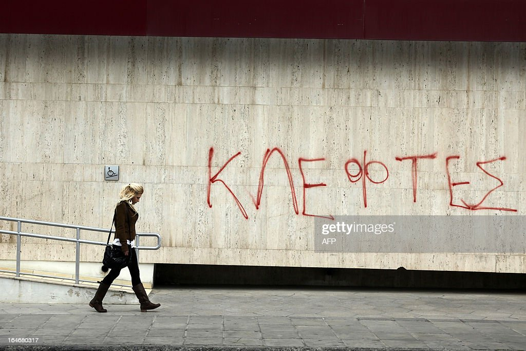 A woman walks past a of wall of a Laiki bank branch which has graffiti on it reading in Greek: 'thieves' in the Cypriot capital, Nicosia, on March 26, 2013. The bailout agreed in Brussels on March 25 hits investors with deposits of over 100,000 euros at both Bank of Cyprus and at Laiki, the island's number two lender, and calls for the effective wrapping up of Laiki. AFP PHOTO / YIANNIS KOURTOGLOU