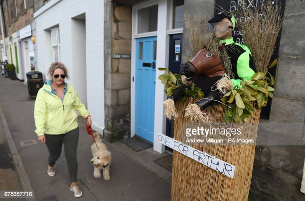 A woman walks past a One for Arthur scarecrow on display during the Elie Scarecrow festival in Elie Scotland