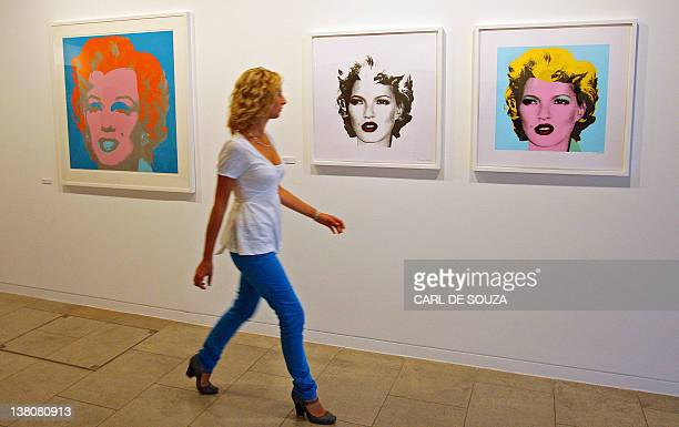 A woman walks past a painting of Marilyn Monroe by Andy Warhol and pictures of Supermodel Kate Moss by Modern artist Banksy during an exhibition in...