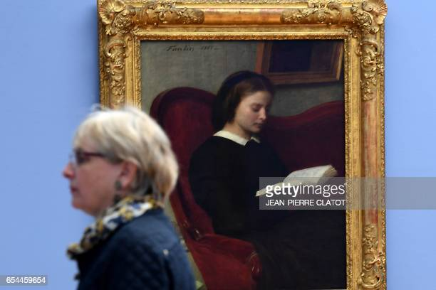 A woman walks past a painting titled 'La Liseuse' painted in 1861 by French painter Henri FantinLatour and displayed during the retrospective...