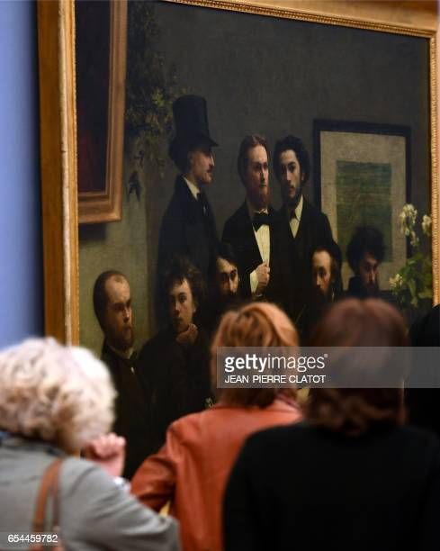 A woman walks past a painting titled 'Un coin de table' painted in 1872 by French painter Henri FantinLatour and displayed during the retrospective...
