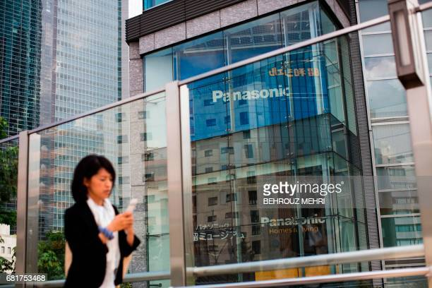 A woman walks past a Panasonic building in Tokyo on May 11 2017 Panasonic released its fullyear earnings until end of March 2017 / AFP PHOTO /...