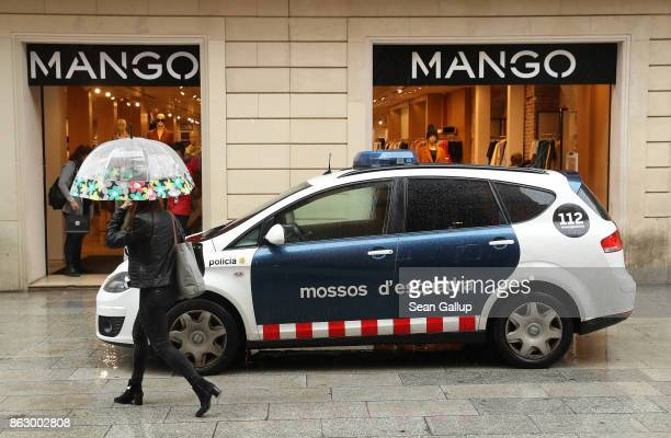 A woman walks past a patrol car of the Mossos d'Esquadra the Catalonian regional police force on October 19 2017 in Barcelona Spain Catalonia's...