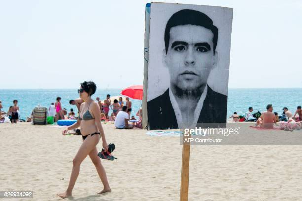 A woman walks past a photograph of a dead migrant on Barcelona's Bogatell beach during an action called by pro human rights organizations 'Tanquem...