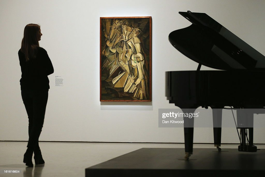 A woman walks past a piece of work entitled 'Nude Descending a Staircase' by Marcel Duchamp during a press preview of 'The Bride and the Bachelors'...