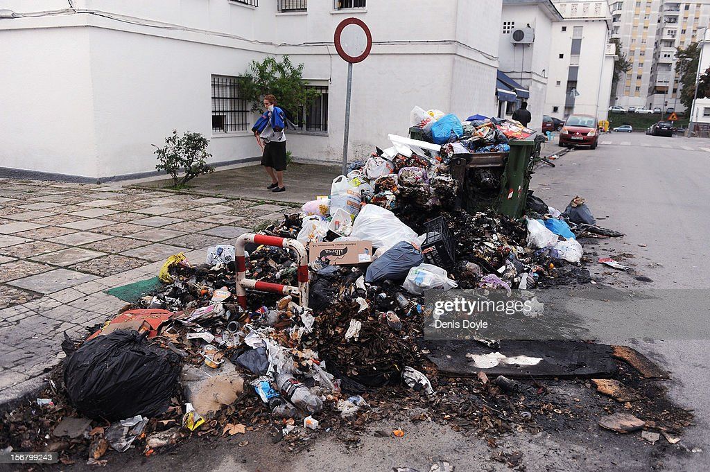 A woman walks past a pile of burnt uncollected garbage during the 20th day of the garbage collectors strike on November 21, 2012 in Jerez de la Frontera, Spain. The garbage collectors are protesting planned layoffs in the sector by the local town council.