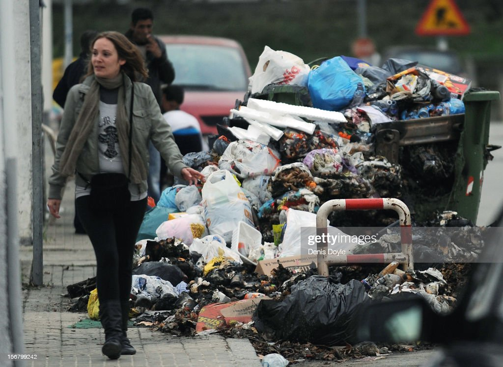 A woman walks past a pile of uncollected burnt garbage during the 20th day of the garbage collectors strike on November 21, 2012 in Jerez de la Frontera, Spain. Residents have begun burning the garbage during the strike by the collectors who are protesting planned layoffs in the sector by the local town council.