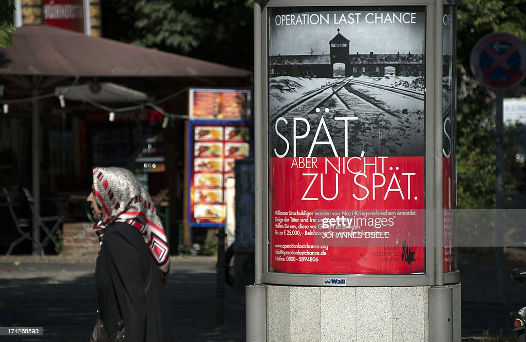A woman walks past a placard featuring a black-and-white photograph of the Auschwitz-Birkenau death camp and the tagline: 'Late but not too late' as a campaign of Nazi-hunting Simon Wiesenthal Center seeking information on the last perpetrators of the Holocaust still at large nearly 70 years on, is pictured on July 23, 2013 in Berlin.