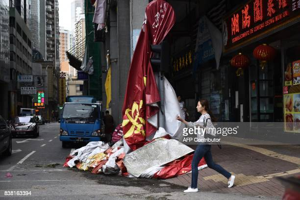 A woman walks past a plastic advertising sign draped over a traffic light in Macau on August 24 a day after Typhoon Hato hit the city The death toll...