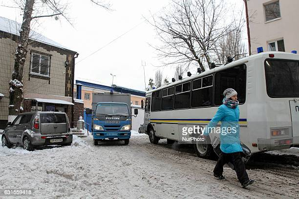 A woman walks past a police vehicles parked next to a Lukyanivske PTDC where a prisoner cut his ear to protest overnight into January 12 2017 in Kyiv...