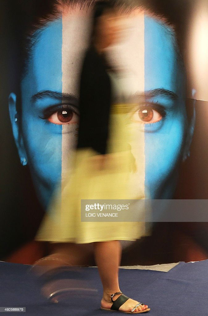 A woman walks past a poster advertising Argentinian Cinema at the International Film Market held on the sidelines of the 67th edition of the Cannes Film Festival in Cannes, southern France, on May 21, 2014.
