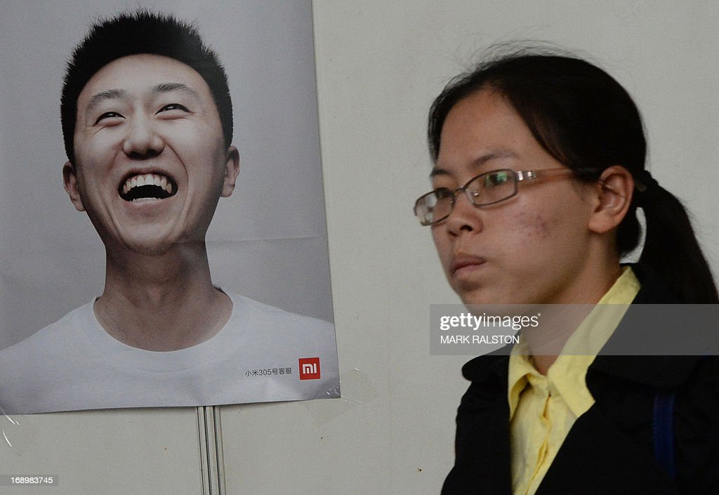 A woman walks past a poster as she attends a jobs fair in Beijing on May 18, 2013. Chinese state media has reported that the China will need to find employment for a record number (seven million) of college graduates this year as the country's economy continues to slow. AFP PHOTO / Mark RALSTON