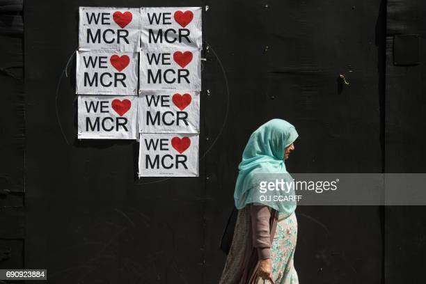 TOPSHOT A woman walks past a poster displaying a message of defiance to the terror attack of May 22 at the Manchester Arena in Manchester northwest...