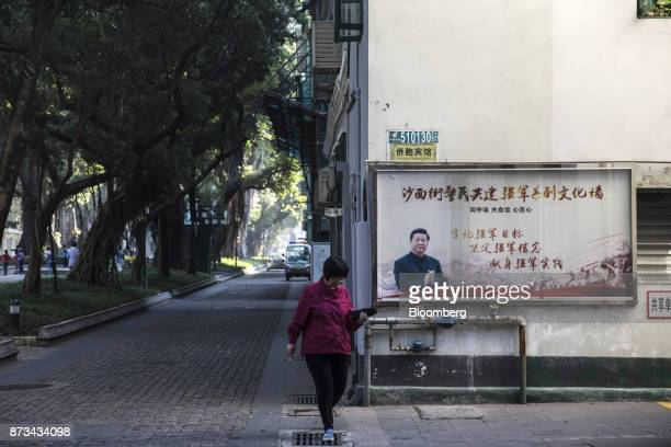 A woman walks past a poster featuring a photograph of China's president Xi Jinping on Shamian Island in Guangzhou China on Thursday Nov 2 2017...