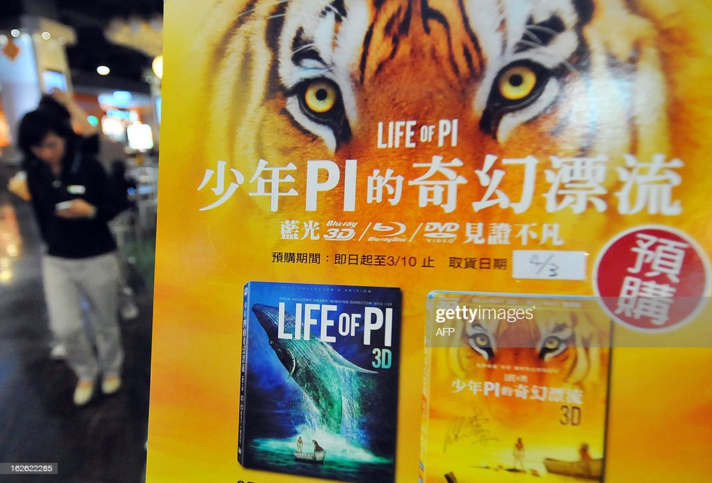 A woman walks past a poster promoting the sales of a DVD featuring Taiwan-born director Ang Lee's 3D spectacular 'Life of Pi' outside a theatre in Taipei on February 25, 2013. Taiwan basked in reflected glory after film-maker Ang Lee won the best director Oscar for fantasy epic 'Life of Pi', which he shot on the diplomatically isolated island where he was born. AFP PHOTO / Mandy CHENG