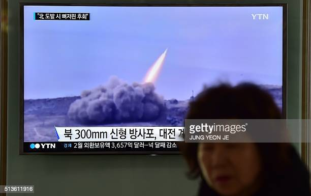 TOPSHOT A woman walks past a public television screen showing file footage of a North Korean missile at a railway station in Seoul on March 4 2016...