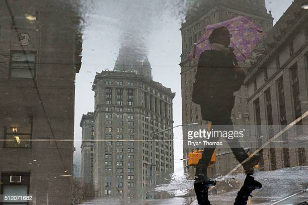 A woman walks past a puddle in the Financial District on February 24 2016 in New York NY According to the National Weather Service as much as 15...