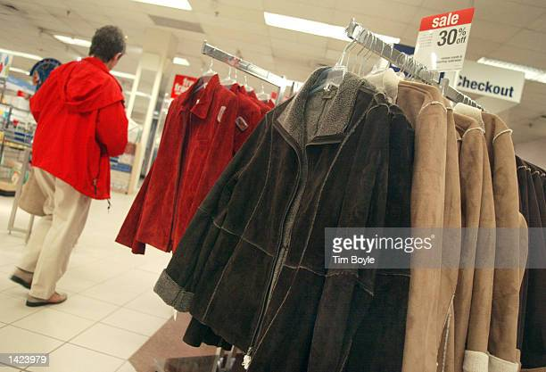 A woman walks past a rack of winter coats at a Sears store September 20 2002 in Niles Illinois With the end of summer approaching this weekend and...